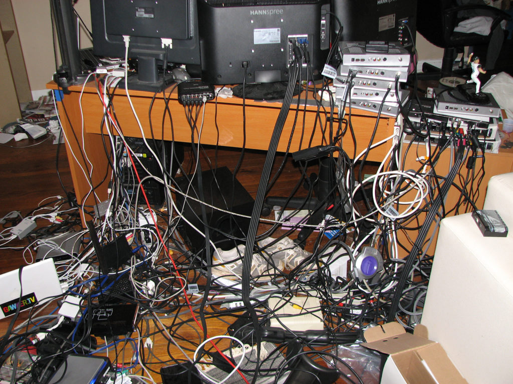 A significant quantity of hardware, terminals, power sources, and connector cables of all sorts are pictured. Three black matte monitors are shown from behind, sitting on a wooden desk stained to a finish like cherry. The right (sinister) two of the monitors are legibly marked HANNspree, one of these disappearing at its top edge into the top right edge of the image. At least ten boxes, of indistinguishable type to this editor, are arrayed on the right (sinister) edge of the desk, upon one of which the muscular miniature figurine of a baseball player is place, in white uniform and blue cap, right arm raised and right leg lifted, midthrow. On the floor, which is of a darker stain than the desk, like black cherry, many cables and other hardware are tangled and arrayed, as well as a pair of lightgray sneakers with white accents. A white hardware shell is visible in the bottom left corner of the image, on which a black sticker with red, blue red, drab, green, and yellow lettering indicates GAMERTV.