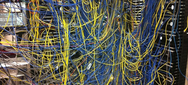 In chief, this image shows a significant tangle of yellow and blue cables, behind which are variously visible hardware stacks in black and chrome. One or two red or orange cables are visible wrapped among the yellow and blue. The tangle is denser at the center of the image, with more yellow cable on the left, and more chrome hardware, and more blue cable and black hardware on the right.
