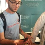 Isaac, who has light brown skin, and short brown hair and beard, is shown standing before a poster presentation. Isaac wears rounded rectangular glasses, a blackstrapped backpack, and a light blue shortsleeved tee, which reads FOLLOW ME in red letters, and which, over the lettering, shows a ladybug with a dotted flight line trailing behind it. In the right hand, Isaac holds a large black insect that might be a cockroach; on the left forearm, a black rectangular tattoo is visible.