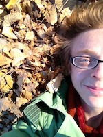 Alix is shown, the left side of the face and shoulders, lying upon brown and yellow leaf litter. Alix has pale skin, and red or auburn hair of several inches length. Alix wears narrow oblong glasses with black frames, a red collared shirt, and a mint green hooded jacket.