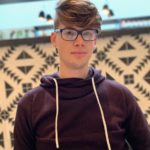 Jacob is shown from above the waist, standing before a white screen or panel patterned with a dark geometric motif. Jacob has light skin, and blond or auburn hair styled in a pompadour above, and shaved close at the sides. Jacob wears eyeglass with black rounded rectangular frames, and a dark wine colored hooded sweatshirt with a pale shoelace drawstring.
