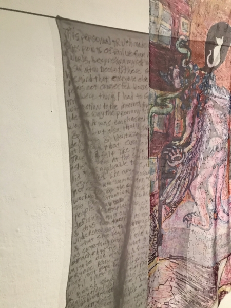 """On black cords, two hangings of sheer cloth or transparent paper are shown, up close, from the side, and obliquely. In the hanging in front and rightmost, a humanoid figure is shown, of incarnadine color, with feathered arms, clawed hands and feet, and blebs and serpents upon its back and head. The figure stoops toward a gray portal barred with vermillion. Above the figure, in a round black niche in a brick red wall, a white cat sits, facing away. The figure walks with a black cane or walker. In the leftmost hanging, hand printed text predominates, largely illegible. The first line might read """"This personal truth makes""""."""