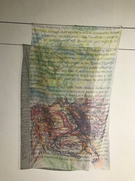 """On black cords, two hangings of sheer cloth or transparent paper are shown. On the front hanging, there is an image of mostly abstract linework. Yellow, green, and blue hues predominate above; a darker and warmer tangle occupies the lower half. All of the hanging is printed with text in black Times, of which evident phrases include """"through their repetition within commodity culture"""", """"carries market value. The effort to name the"""", """"will always fail and ought to"""", """"how do normative gender presump"""", """"which we come to see"""", and """"Gender Trouble offers to explain the"""". The rear hanging is completely covered with hand printed text."""
