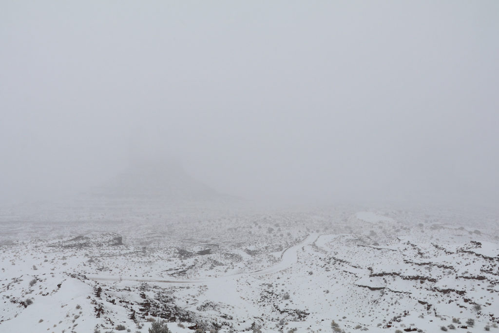 Covered in snow and fog, Monument Valley just visible by the outline of its base.
