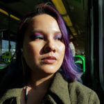 Erika is pictured sitting on a bus, looking to the left (dexter) in 2/3 profile. Erika has brown skin, and hair that is purple with hints of red and electric blue, darker to black underneath. Erika wears eye shadow that is blue at the lids, changing to magenta below the brows. Erika wears an open olive drab wool overcoat, with a wide, pointed collar. Erika wears gray earbud headphones, of which just the volume control is visible below her neck.