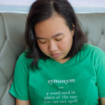 "Saquina is shown seated on a gray, tufted leather seat, looking downward. Saquina has dark hair that falls just below the shoulder, and light brown skin. Saquina wears a mint green shortsleeved tee shirt, on which is printed, in lowercase white italic lettering, ""synonym"", then in lowercase white lettering, ""a word used in place of the word you cannot spell""."