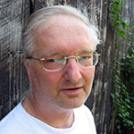 Don is shown before a weathered grey wooden wall or slat fence. Don has pale skin and short grey hair, receding from the forehead. Don wears rectangular eyeglasses, and a white crewneck shirt.