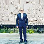 Walid is shown before a wall of carved marble or sandstone with foliage and a half-height cast iron fence below Walid is shown standing at full-height. Walid has light to medium toned skin and little visible hair. Walid wears a dark navy or black suit and black shoes, with a pale collared shirt and pale necktie beneath.
