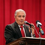 Farouk is shown before a cardinal red curtain, standing at a podium which supports two microphones. Farid has light brown skin and short white hair. Farid wears a heavy black suit with notch lapels, with a white collared shirt beneath, and a thick red necktie of the same cardinal hue as the curtains.