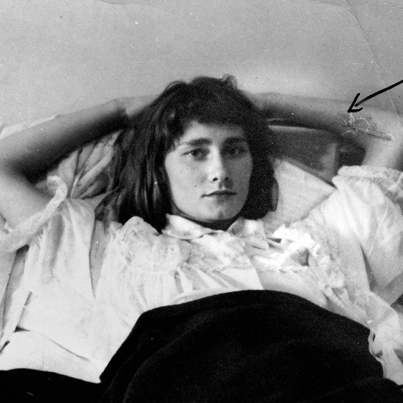 In a grayscale image, Halina is shown, reclining before a pale wall. Halina has pale skin and dark shoulderlength hair, with shorter bangs. Halina wears a ruffled white shortsleeved blouse, with a dark skirt or blanket below. Halina's arms are cradled upon a pillow or upholstered surface, behind the head.