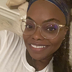 A photo of a Black woman smiling and wearing gold-rimmed glasses and a white T-shirt.