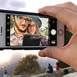 Ryan and Karolina are shown, within the frame of an iPhone's Photos app, as captured by the rear facing camera. Ryan has pale skin, and short reddishbrown hair, chinstrap beard, and mustache; Karolina has pale skin, and long blond or auburn hair. Both Ryan and Karolina wear round rimmed eyeglasses, and floral shirts in red, blue, and purple hues. Ryan's shirt is collared and paler in color. Karolina wears a black widebrimmed hat. The iPhone is white, with a black case, and held in a pale hand between thumb and forefinger. Ryan or Karolina are seen to hold a black-cased phone, which has captured the image here described. Behind the iPhone, persons can be seen seated along a stonewall, before a rustcolor tree, and sunlit sky or sea.