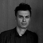 In a grayscale image, Tom is shown, before a dark paneled wall. Tom has pale skin and dark hair, which is short at the sides and longer at the crown. Tom wears a dark blazer or jacket with notch lapels, and a dark shirt beneath.