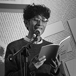 In a grayscale image, Yaxkin is shown standing behind a microphone, before a pale wall upon which lines of text in abstract arrangements are printed or projected. Yaxkin has light to medium toned skin, and short dark curly hair. Yaxkin wears rounded rectangular eyeglasses, and a dark crewneck sweater over a light collared shirt, and holds an open paperback book with both hands.