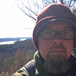 Andy is shown before russet foliage, a bare tree, water, and sky bright sky. Andy has light skin, a thick grey goatee, and a shorter grey mustache. Andy wears rectangular eyeglasses, a red felt cap over a brimmed cap, and a khaki or olive drab stand collar jacket.