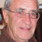 Anthony is shown, close up, before a beige wall. Anthony has pale skin and grey hair. Anthony wears rectangular eyeglasses, and a brown ribknit turtleneck sweater.