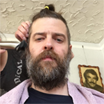 A photo of a white man with a long beard and long hair. He appears to be getting a haircut, though the photo is ambiguous. A photo can be seen over his left shoulder, resembling Burt Reynolds.