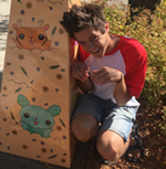 Ryan is shown before yellowgreen foliage, and beside a board painted with kawaii mammals, one goldenrod yellow in color, the other seafoam. Ryan has pale skin and thick brown hair which stands on end. Ryan is kneeling, with arms bent at the elbows and wrists, and held at chest height. Ryan wears a white shortsleeved tee shirt with red raglan sleeves, and denim shorts in a pale blue wash.
