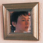 A photo of a white person looking away  from the camera, reflected in a gold-framed mirror mounted on a peach-colored wall. They have dark short hair and dark eyes, and their mouth is slightly open.