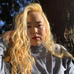Mihee is shown, before the trunk of a tree. Mihee has light skin, long bright blond hair, and black eyebrows. Mihee wears a light grey turtleneck.