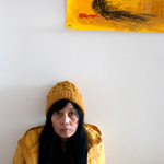 A photo of a Japanese-Spanish woman wearing a yellow knit cap and a black shirt with a yellow shell. Part of her comic is displayed above her, as she occupies the bottom left-hand corner of the photo.