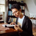 Lakan is shown seated at a wooden table, before a white wall, a dark wooden bookcase, and a window admitting daylight. Lakan has light brown skin and short dark curly hair. Lakan wears rectangular frame eyeglasses, a white tee shirt with a print in muted browns, and a black cardigan or zipped-open hooded sweatshirt. Lakan holds a book or notebook upon the tabletop, open in both hands.