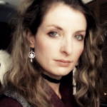 Jessica is shown before a grey ceiling and dark wooden door. Jessica has pale skin, and blond hair which is dark at the roots, and falls below the shoulders. Jessica wears eyeshadow, a silver circled-star-with-pendant earring, a black band choker, a red sweater or blouse, and a grey vest.
