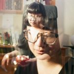 In a double exposure, Jane is shown before a white wall and a wooden bookshelf. Jane has black hair with cut bangs, that otherwise falls about the chin, and light skin. Jane wears a half-sleeved black v-neck blouse or dress, and hornrim eyeglasses. Jane is seated, and holds half of a large reddish orange citrus fruit, or pomegranate.
